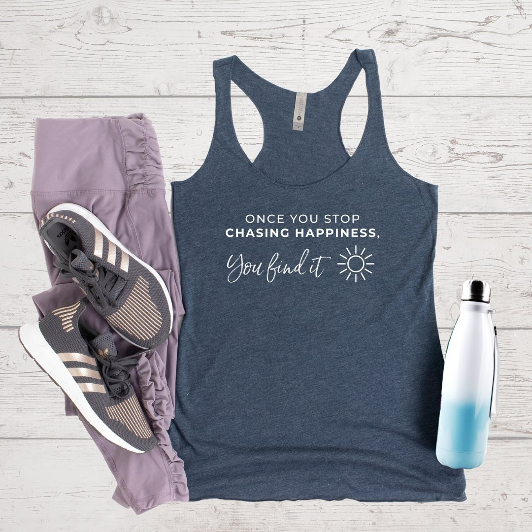 How will you ever have happiness right now if you believe it's somewhere else?⁣⁣Our tanks come in Indigo (pictured), Envy, and Vintage Purple tri-blend... and are super soft and comfortable. Perfect for working out, running errands, or just lounging.⁣⁠⁣5% of net proceeds goes to @mentalhealthamerica.